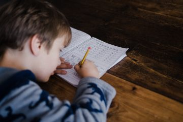 Child working on maths on a wooden table